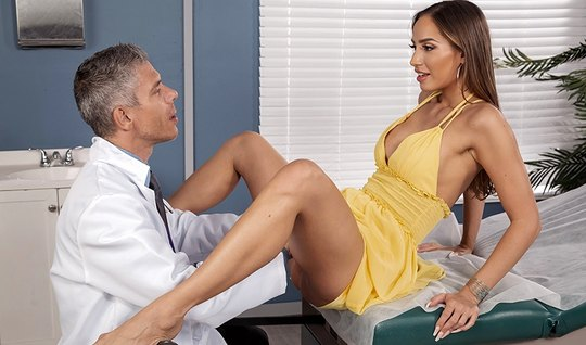Brunette with long legs in the doctors office spreads her legs